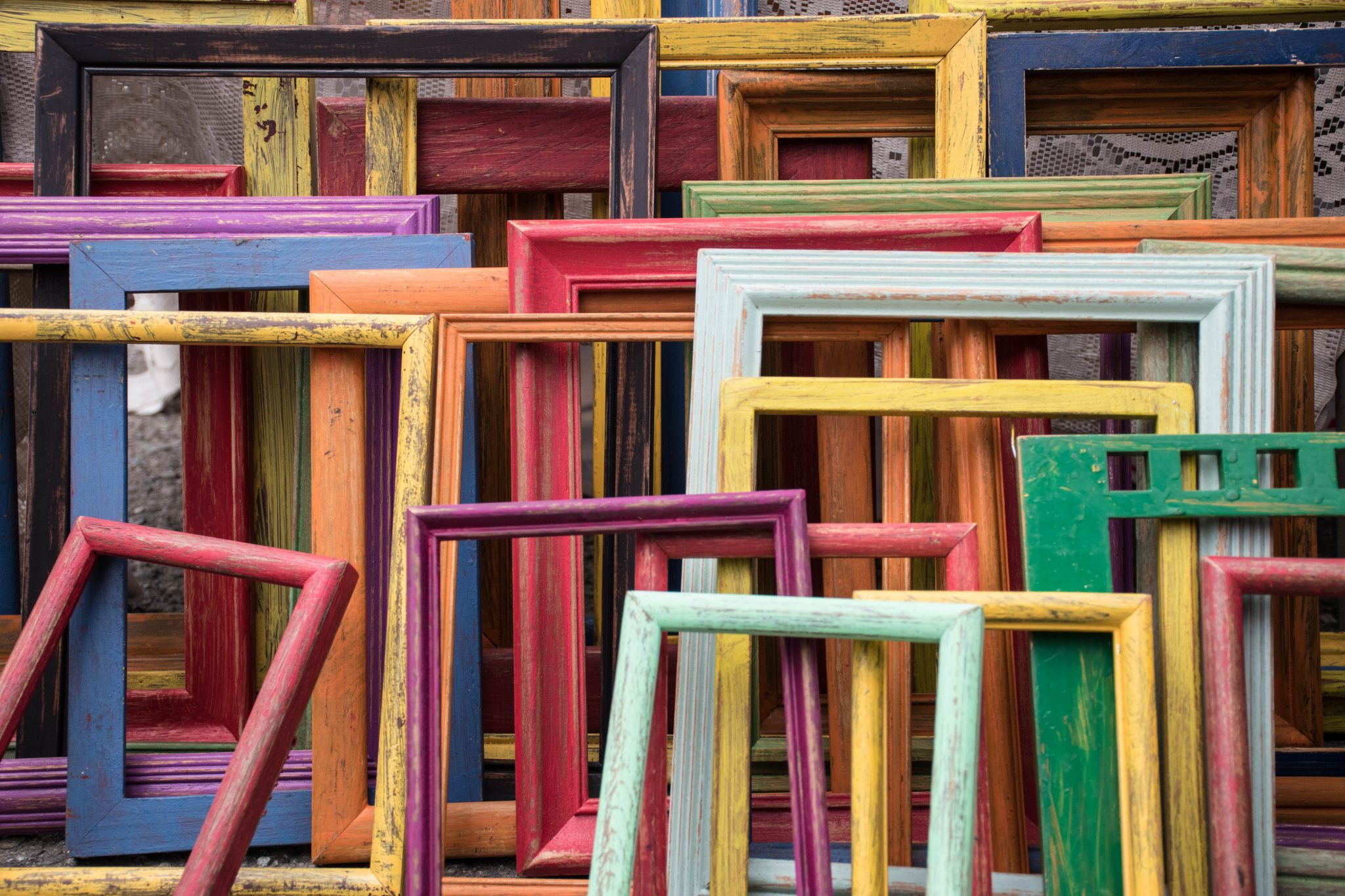 Stack of picture frames in multiple colors and sizes